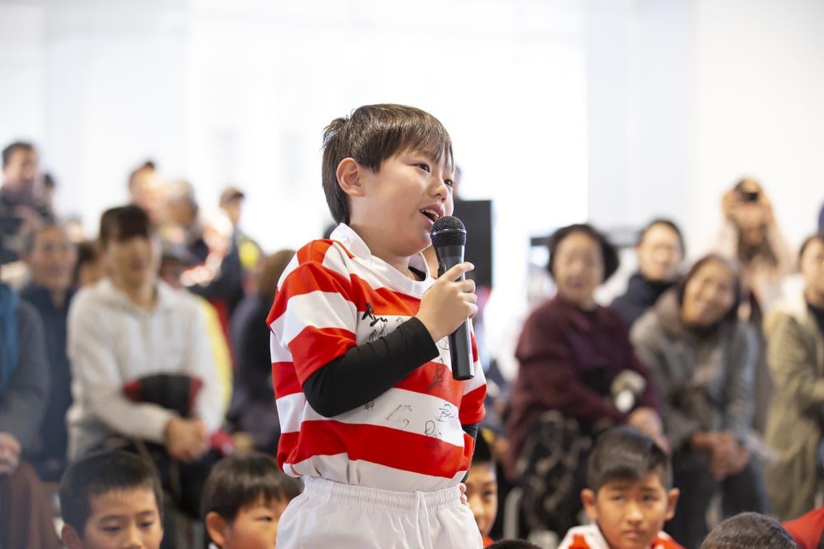 ラグビーをする子供が選手に質問をする姿