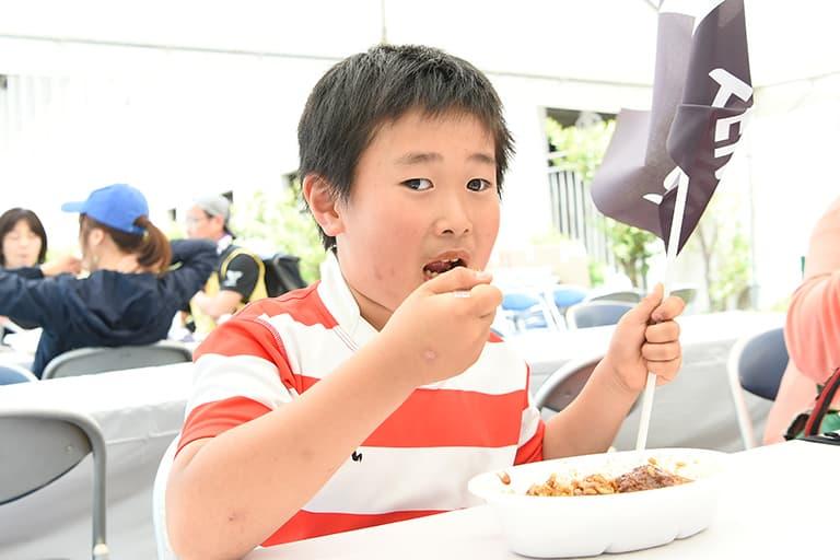 天理大学ラグビー部ファンブース Non title caféでKatsuiのカレーを食べる子供